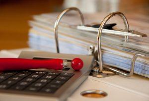 Dokumenty w segregatorze, długopis i kalkulator